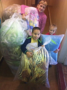 Children helping with bedding for refugees